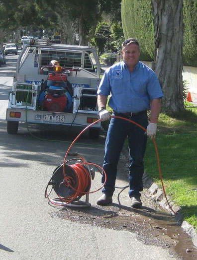 Morgan hill plumbing contracor runs drain cleaning equipment at a curb